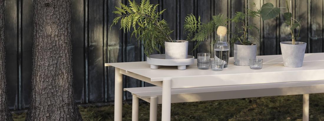 Linear Steel Bank und Tisch in weiss von Muuto in der Ambienteansicht. Tisch und Bank können aufgrund ihrer Fertigung aus Stahl perfekt im Garten genutzt werden und begeistern mit ihrem modernen Design.