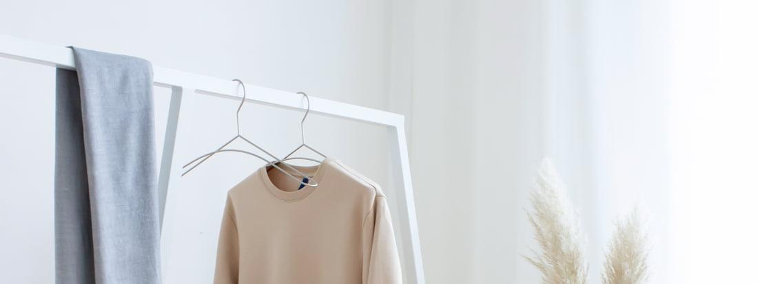 Skandinavisch schlicht wirkt die Kombination von weisser Garderobe, schwarzen Metall-Kleiderbügeln und einer kleinen Holzbank. 3 Must Haves für ein gelungenes Ankleidezimmer.