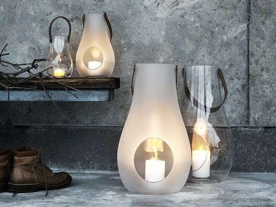 Ein Paradebeispiel für stilvolle und schöne Geschenke für Frauen: die Design with Light Laterne von Holmegaard aus durchsichtigem bzw. matt-weißem Glas und einem Tragegriff aus Leder.