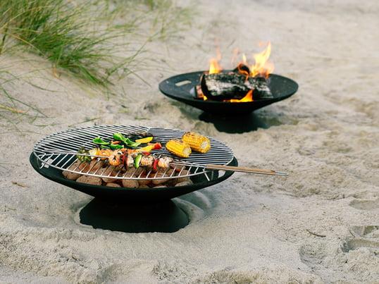 Die Helios Feuerstelle von Skagerak sorgt für eine gemütliche Atmosphäre und Stimmung im Garten. Sie ist aber auch mit dem zugehörigen Edelstahlrost perfekt zum Grillen geeignet.