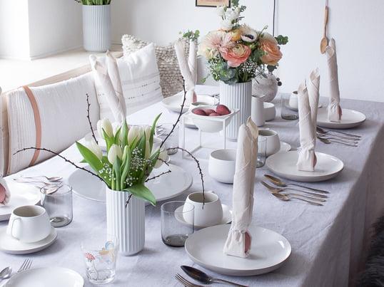 Deko-Ideen zu Ostern - Pepper Schmidt setzt auf die Lyngbyvasen in Weiss und Grau von Lyngby Porcelæn, die Ovale Schale von Alessi in Weiss und die Tischdecke in Grau aus Leinen von Alfred.
