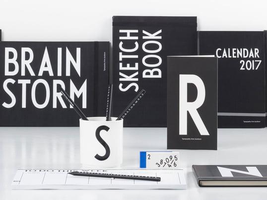 Design Letters bietet vom schwarz-weissen Notizbuch bis zum AJ Bleistift alle Utensilien für die Schule und das Büro. Arne-Jacobsen-Buchstaben verleihen Becher, Buch und Kalender eine persönliche Note.