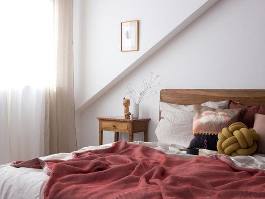 Pepper von heimatbaum.com zeigt uns, wie sie ihr Schlafzimmer mit der Ripple Decke von Muuto und dem Knot Kissen von Design House Stockholm in Rot- und Erdtönen gestaltet.