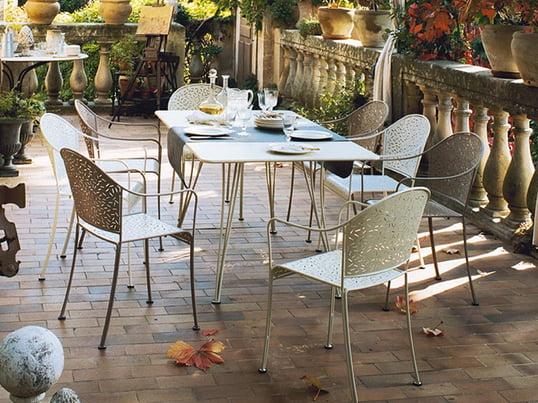 Der Rendez-Vous Tisch und Stuhl von Fermob wirkt im Garten gemütlich und romantisch. Dank des pflegeleichten Materials und der Aussparungen ist es besonders wetterbeständig und langlebig.